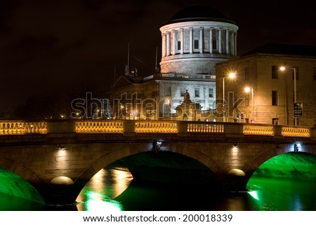 Four Courts and bridge over river Liffey illuminated at night in the city of Dublin in Ireland. - stock photo