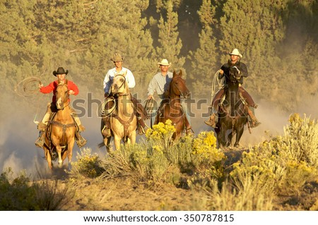 Four Cowboys riding together in beautiful light - stock photo