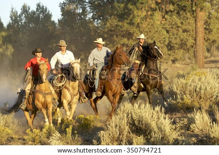 Four Cowboys riding together in beautiful light
