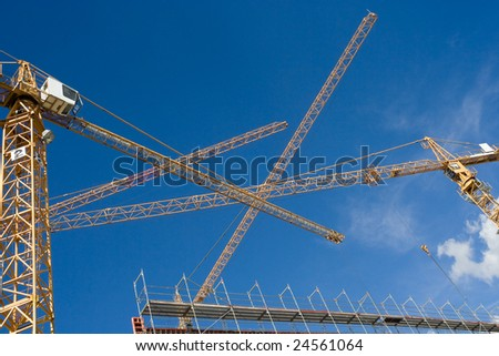 four cranes building a new industrial building - stock photo