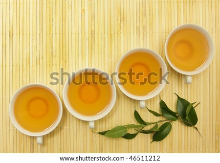 four cups of tea and green leaves on the mat - stock photo