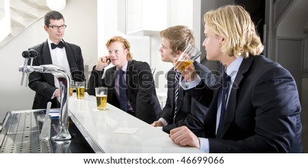 Four customers around a bar, being served by a barman - stock photo
