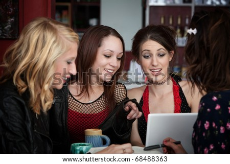 Four cute college girls with a laptop having fun in a cafe over a coffee