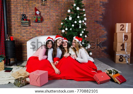 Four cute friends girls wear on warm sweaters, black pants and santa hats against new year tree with christmas decoration at studio with 2018 boxes.