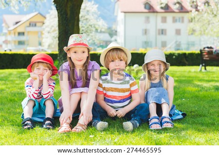 Four cute kids sitting in a row in the park, wearing hats - stock photo