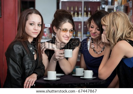 Four cute teenaged girls hanging out in a cafe