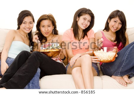 Four cute young women sitting on a sofa with snacks
