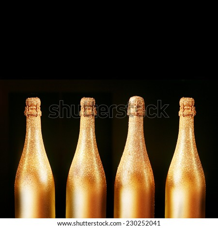 Four decorative gold bottles of luxury champagne over a black background with copyspace for your New Year, Christmas or wedding greeting or invitation, square format - stock photo