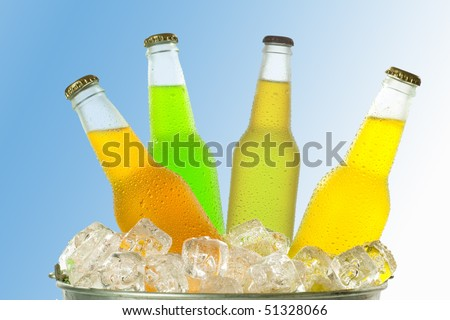 Four different color wet glass bottles in bucket with ice cubes on gradient blue to white background - stock photo