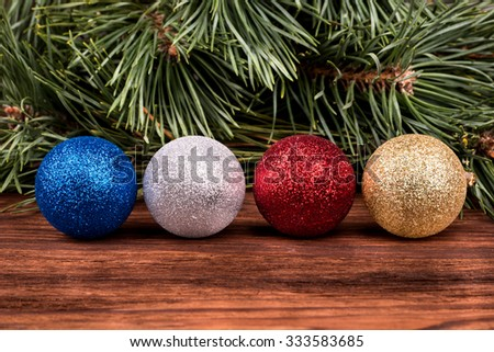 Four different colored Christmas balls on the background of pine branches - stock photo