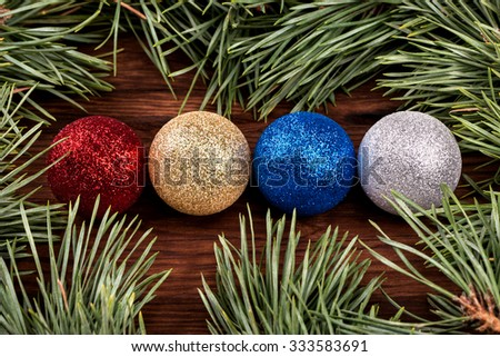 Four different colored Christmas balls surrounded by pine branches - stock photo