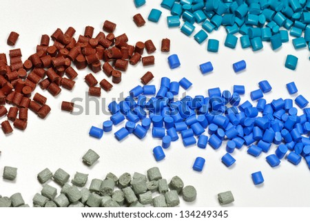 four different dyed plastic granulates for injection moulding industry - stock photo