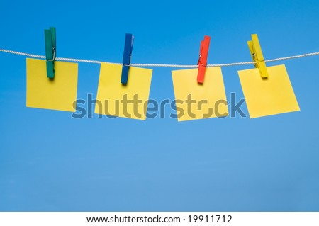 Four different post it hanging out with colorful pegs in a sunny day. Write it on whatever you want!