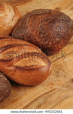 four different rye and white flour fresh french bread loaf on light wooden table