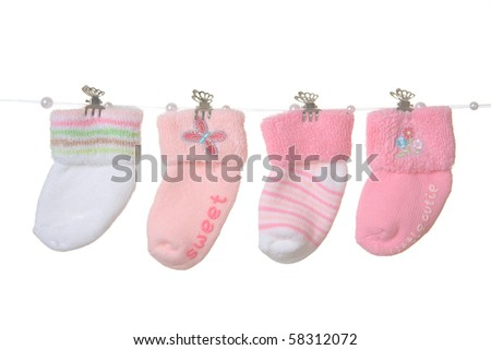 Four different socks for baby girl hanging on rope, isolated. - stock photo