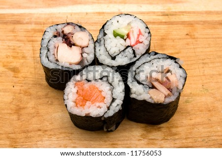 Four different sushi rolls on cutting board. - stock photo