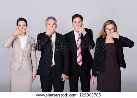 Four diverse businesspeople standing in a row gesturing for silence in a conceptual representation of the saying - Speak no evil - stock photo