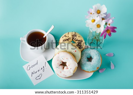 Four donuts on saucer with cup of tea. Aquamarine background - stock photo
