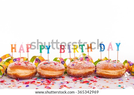 """four doughnuts with confetti and streamer - birthday decoration with candles with copy space on upper section of picture - candles with text """"happy birthday"""" - stock photo"""