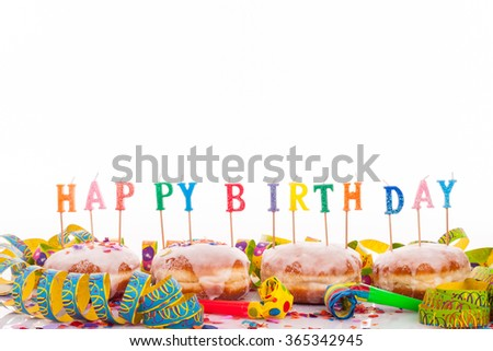 """four doughnuts with with frosting, confetti and streamer - birthday decoration with candles with copy space on upper section of picture - candles with text """"happy birthday"""" - stock photo"""