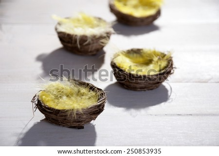 Four Easter Baskets Or Nests With Yellow Feathers in Sunny Light With Copy Space Free Text Or Your Text Here For Happy Easter Greetings Or Easter Decoration Close Up Or Macro Wooden Background - stock photo