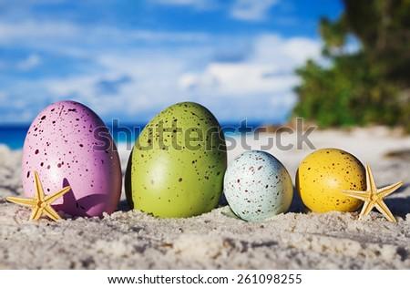 Four easter eggs on ocean beach  - stock photo