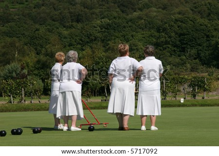 Four elderly females (rear view) dressed  in white lawn bowling outfits and standing on a bowling green. One of the ladies is holding a red metal ball gatherer. Trees and shrubs to the rear. - stock photo