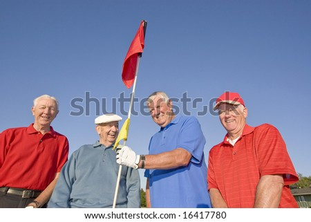 Four elderly men are standing on a golf course.  They are smiling and looking at the camera and one man is holding a flag.  Horizontally framed shot. - stock photo