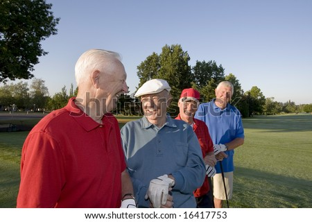 Four elderly men are standing together on a golf course. They are holding their clubs, smiling, and looking at each other.  Horizontally framed shot. - stock photo