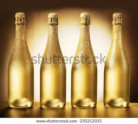 Four elegant unlabeled bottles of luxury golden champagne over a highlighted brown background with frosted necks and glowing contents to celebrate New Year, Christmas or a wedding ceremony - stock photo