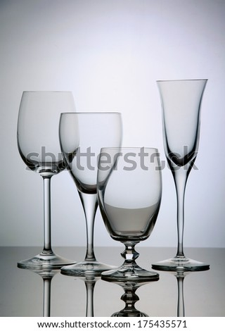 Four empty transparent wine glasses composition