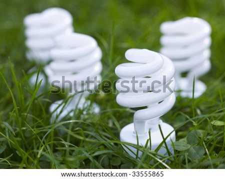 Four energy saving spiral lightbulbs planted in grass - stock photo