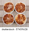 four equal ramekin bowls of homemade macaroni and cheese dinner. top down view - stock photo