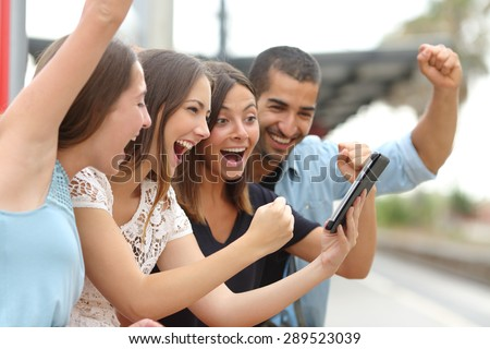 Four euphoric multi ethnic caucasian and arab friends watching tv on a a tablet in a train station - stock photo
