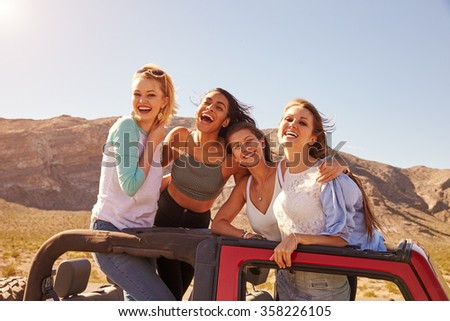 Four Female Friends On Road Trip Standing In Convertible Car - stock photo