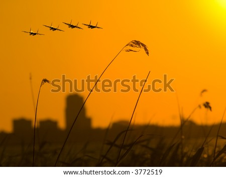 four fighters over sunset with cityscape background - stock photo