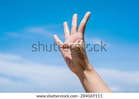 Four fingers on blue sky - stock photo