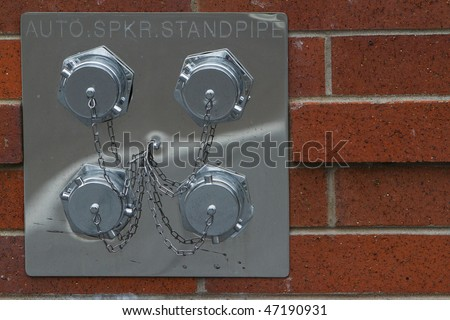 four fire hose connections on the exterior of red brick building - stock photo
