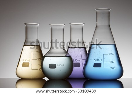 four flasks with colored liquid and a white background