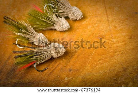 four fly fishing lures on antique wood. - stock photo