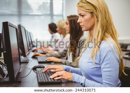 Four focused women working in computer room in the office - stock photo