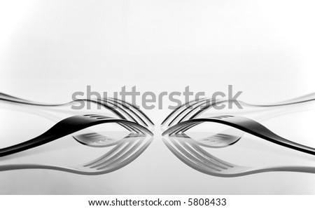 four forks on white reflected in table top - stock photo