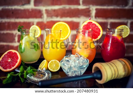 four fresh lemonades with fruits and ingredients - stock photo