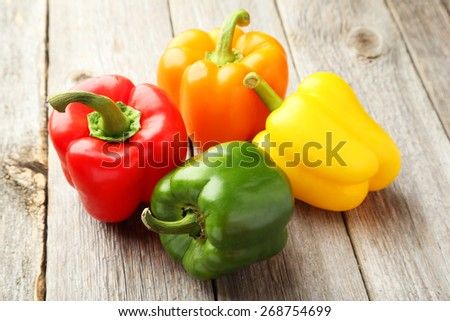 Four fresh pepper on grey wooden background