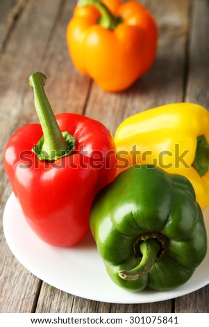 Four fresh pepper on plate on grey wooden background - stock photo