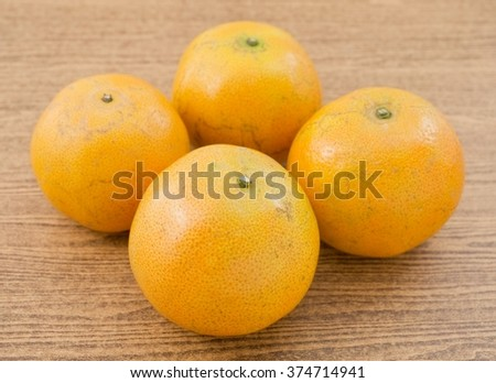 Four Fresh Ripe and Sweet Oranges on A Wooden Table, Orange Is The Fruit of The Citrus Species. - stock photo
