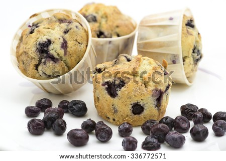 Four freshly baked blueberry muffins and some fresh berries fruit on the foreground.  Two of the background muffins are blur. White background. - stock photo