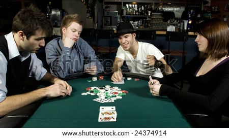 Four friends around table playing poker in bar - stock photo