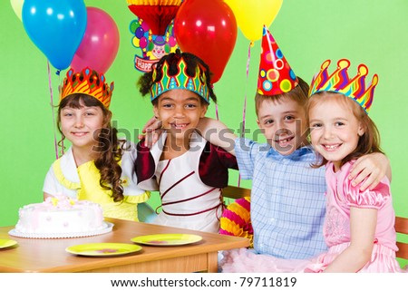 Four friends at the birthday party, embracing - stock photo