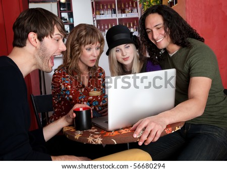 Four friends enjoying a video on a laptop at a cafe - stock photo